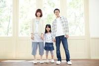窓際に立って手をつないでいる笑顔の父母と女の子のポートレート 02336006086| 写真素材・ストックフォト・画像・イラスト素材|アマナイメージズ