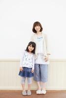 白い壁の前で母親に寄り添う女の子のポートレート 02336006089| 写真素材・ストックフォト・画像・イラスト素材|アマナイメージズ
