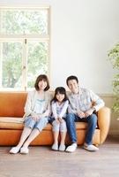 窓際の茶色のソファーに座る父母と女の子のポートレート 02336006091| 写真素材・ストックフォト・画像・イラスト素材|アマナイメージズ