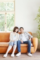 窓際の茶色のソファーに座る笑顔の若い夫婦のポートレート