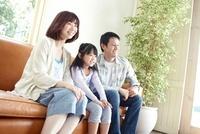 窓際の茶色のソファーに座る父母と女の子 02336006095| 写真素材・ストックフォト・画像・イラスト素材|アマナイメージズ