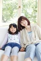 窓際の白いソファーに座る母親と女の子 02336006097| 写真素材・ストックフォト・画像・イラスト素材|アマナイメージズ