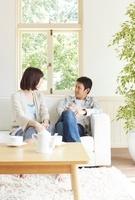 窓際の白いソファーに座り話をしている若い夫婦 02336006100| 写真素材・ストックフォト・画像・イラスト素材|アマナイメージズ