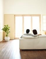 白いソファーに座り窓の外を見ながら話をしている若い夫婦の後姿