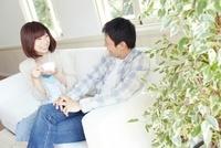 窓際の白いソファーに座り話をしている若い夫婦