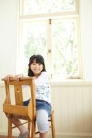 窓際の木製の椅子に座り笑顔の女の子 02336006107| 写真素材・ストックフォト・画像・イラスト素材|アマナイメージズ