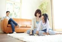 ラグの上で本を読む母と娘とソファーに座り笑顔で見ている父親