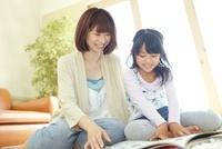 ラグの上で本を読む母親と女の子