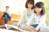 ラグの上で本を読む母と娘をソファーに座り笑顔で見ている父親