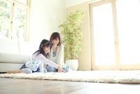 白いラグの上で絵を描いている母親と女の子