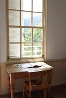 窓際の机に置かれた本と色鉛筆