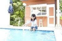 プールの淵に座り水をかけている女の子 02336006165| 写真素材・ストックフォト・画像・イラスト素材|アマナイメージズ