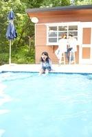 プールの淵に座り水に足を入れている女の子と小屋の前の父母 02336006166| 写真素材・ストックフォト・画像・イラスト素材|アマナイメージズ