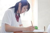 教室でノートをとる女子高生