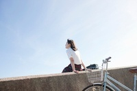 自転車を降りて防波堤に座る女子高生