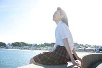 防波堤に座り海を眺めている女子高生