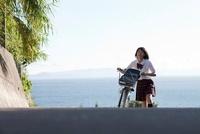 海の見える坂道を自転車を押して上がってくる女子高生