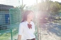 グラウンドのネットに寄りかかっている女子高生 02336006322  写真素材・ストックフォト・画像・イラスト素材 アマナイメージズ