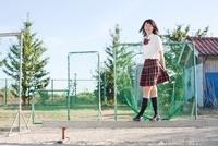 グラウンドに置かれた平均台の上の笑顔の女子高生