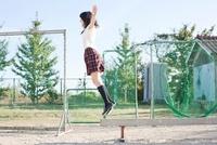 グラウンドに置かれた平均台の上で飛び上がる女子高生