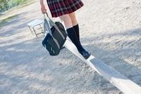 グラウンドに置かれた平均台の上で遊ぶ女子高生の足元