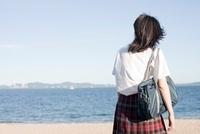 海を見つめている女子高生の後姿