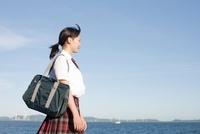 海沿いを歩く女子高生