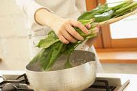 鍋にホウレン草を入れる女性の手元