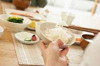 和食を食べる人の手元と白米