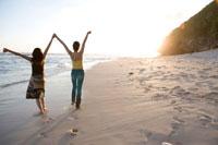 手をつないで浜辺を走る女性