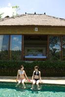 プールサイドに座る水着姿の女性2人