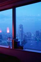 窓から見える夕暮れの隅田川と高層ビル