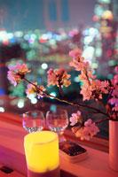 夜景が見える部屋の窓辺に置いた桜の花とグラス