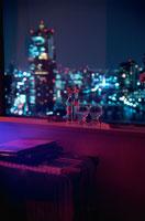 夜景が見える部屋の窓辺に置いたグラスとスーツケース