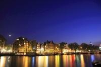 月のあるボートハウスとアムステル川の夜景