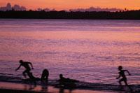 夕焼けの海岸線で遊ぶ子供たち
