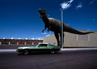 街中で吠えるティラノサウルスレックスと走る車