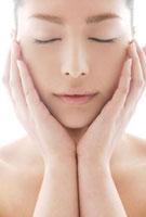 頬に触れる女性のビューティーイメージ
