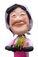 頬被り姿で稲穂を手に微笑む農家の女性