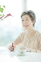 楽譜を書く笑顔の中高年女性