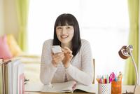 勉強机に座ってスマートフォンを操作する女の子 02381001048  写真素材・ストックフォト・画像・イラスト素材 アマナイメージズ