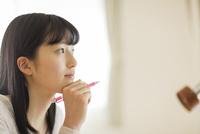 ペンを持って頬杖をつく女の子 02381001067  写真素材・ストックフォト・画像・イラスト素材 アマナイメージズ