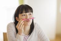 口の上にペンを乗せる女の子