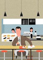 カフェで軽食をとるサラリーマン男性
