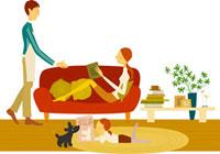 リビングで本を読む母と娘とエプロンをした父親