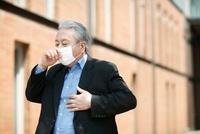 マスクをして咳き込む老年男性