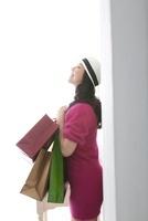 ショッピングバッグを持ち目を閉じて微笑む女性