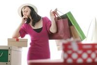 ショッピングバッグとプレゼントの箱に囲まれ微笑む女性