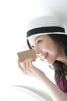 カードを鼻に当て微笑む女性 02441001236| 写真素材・ストックフォト・画像・イラスト素材|アマナイメージズ