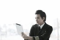 タブレットパソコンを持っているパイロット 02442000613| 写真素材・ストックフォト・画像・イラスト素材|アマナイメージズ